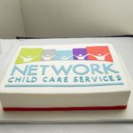 A white cake with the NCCS logo on it