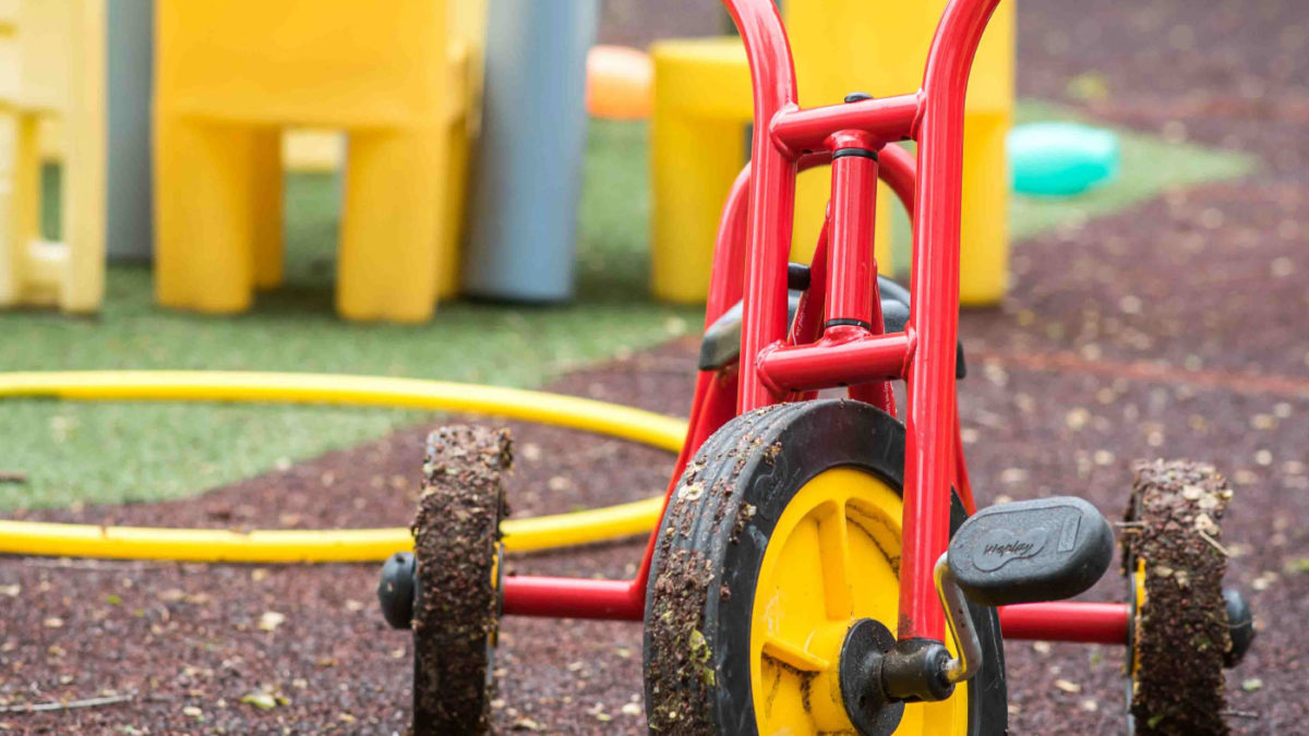 A red tricycle with yellow wheels on a playground