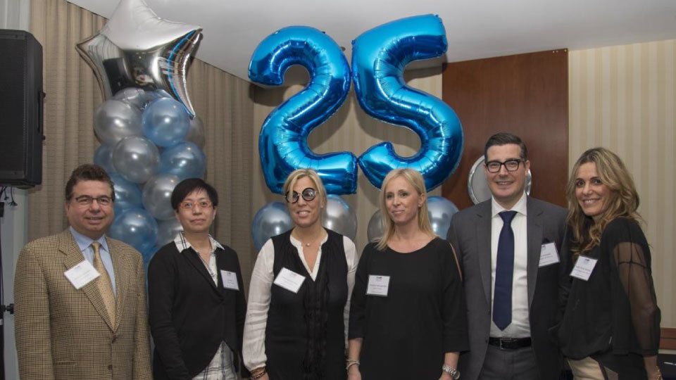 Six staff members posing in front of a blue balloon in the shape of a 25