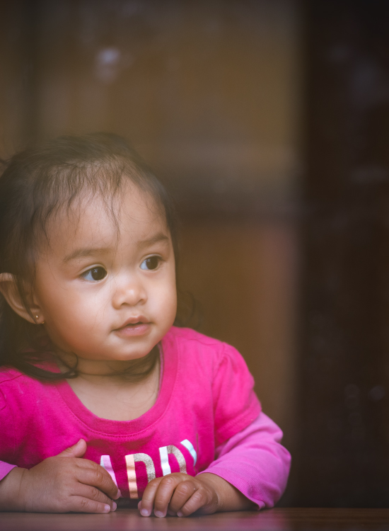 A young asian girl in a pink shirt looking out a window