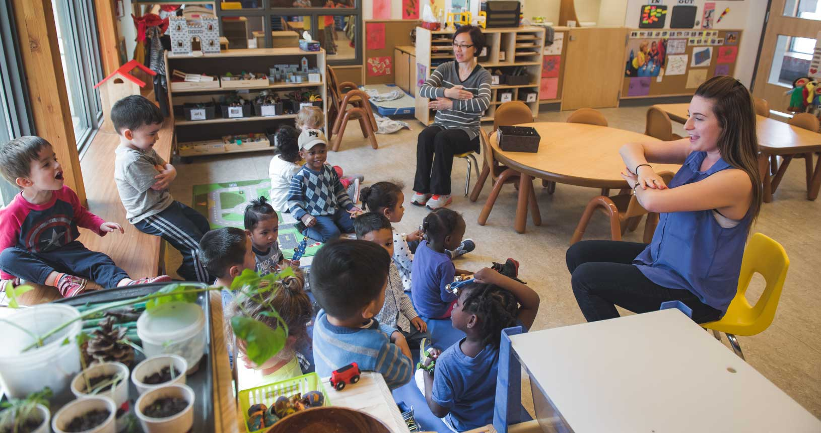An interior shot at Dane Avenue. Two women are teaching a group of children.