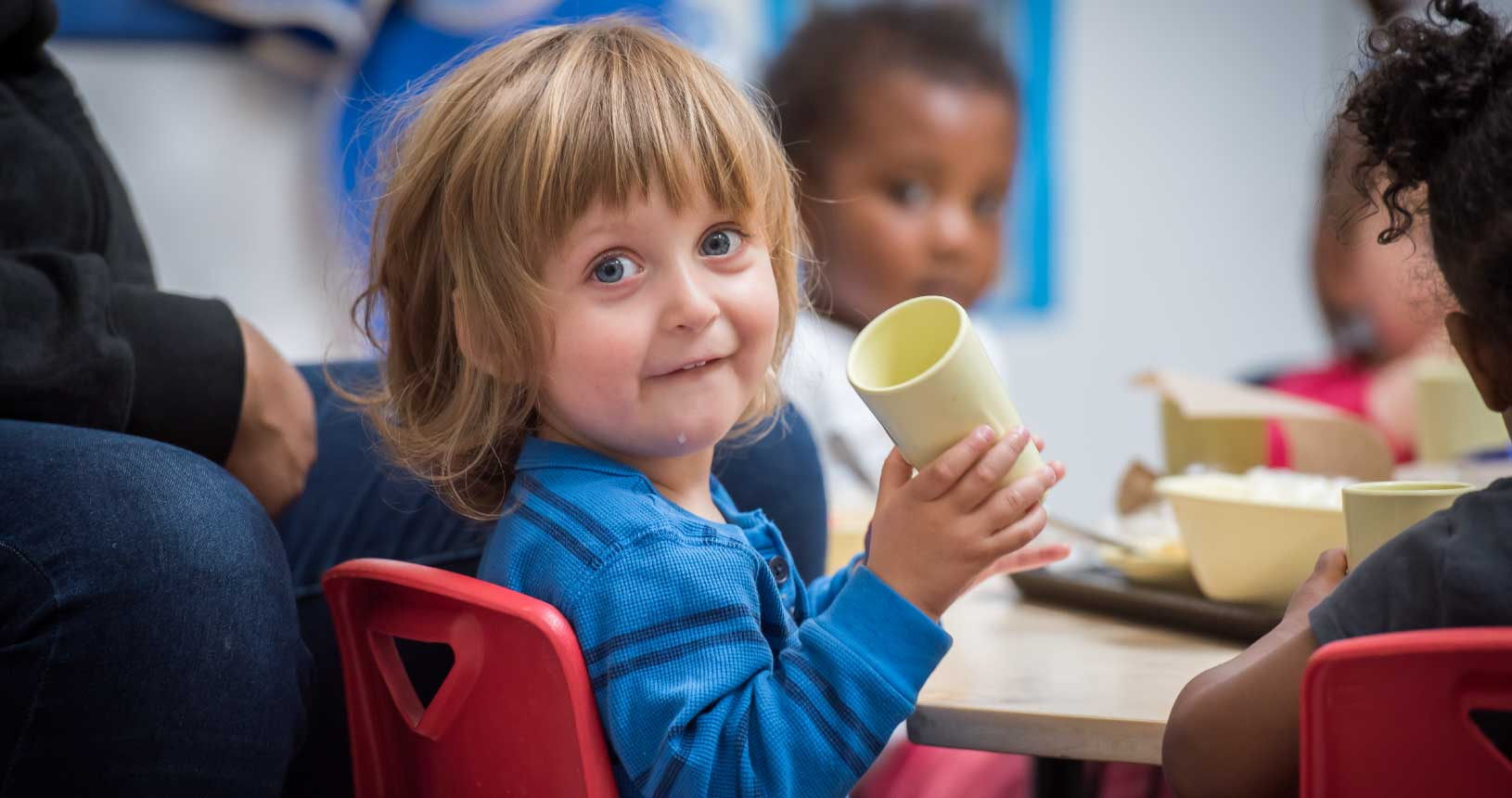 A young child turns to face the camera while holding a cup