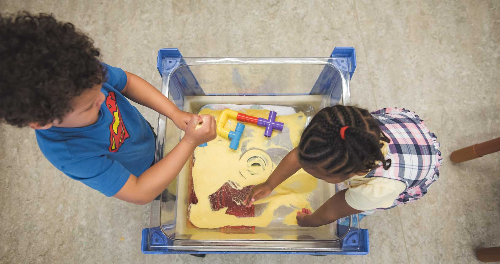 Two children are playing with toys in a box of sand
