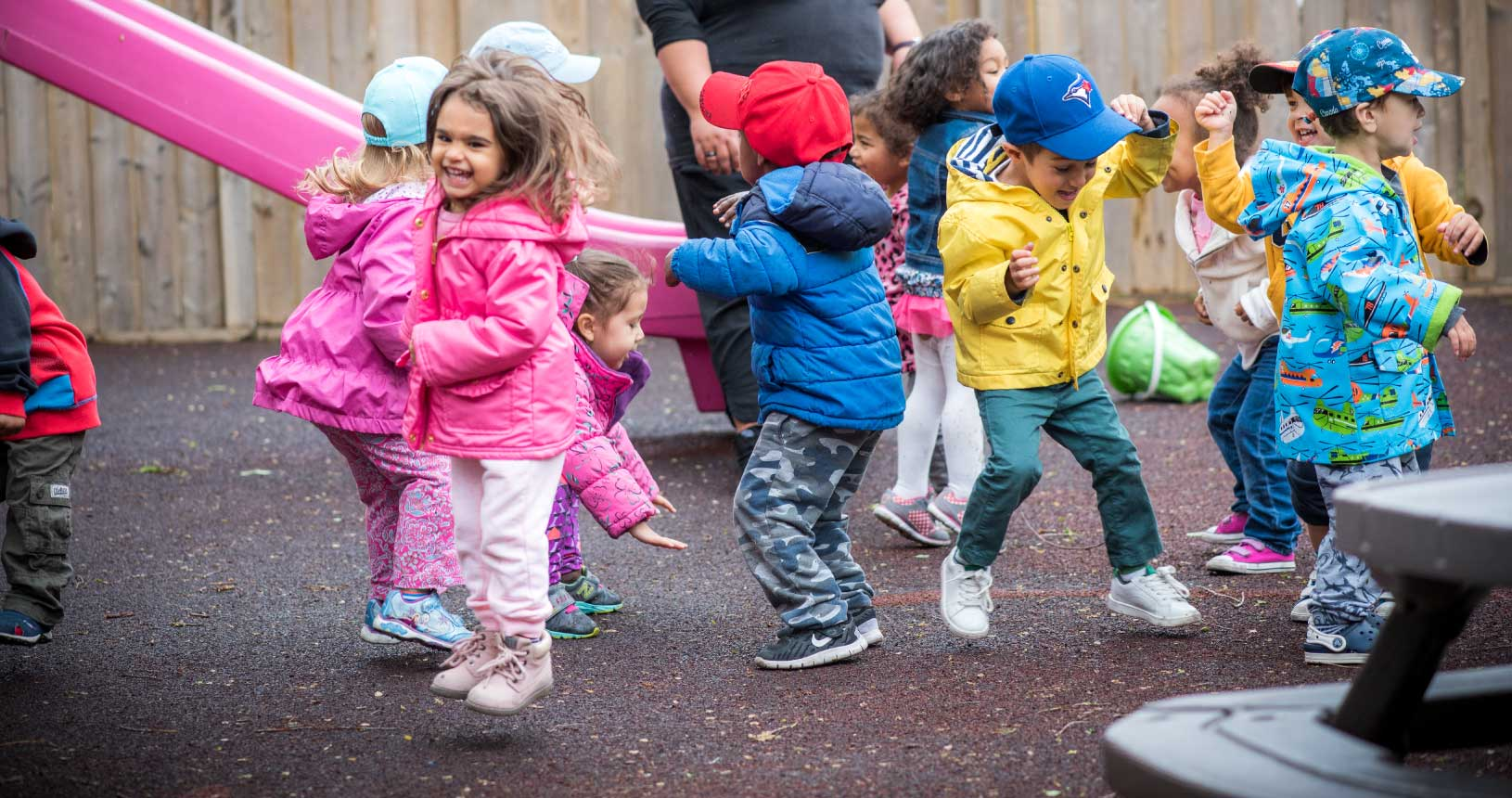 A bunch of children dancing in a circle on the playgrounds