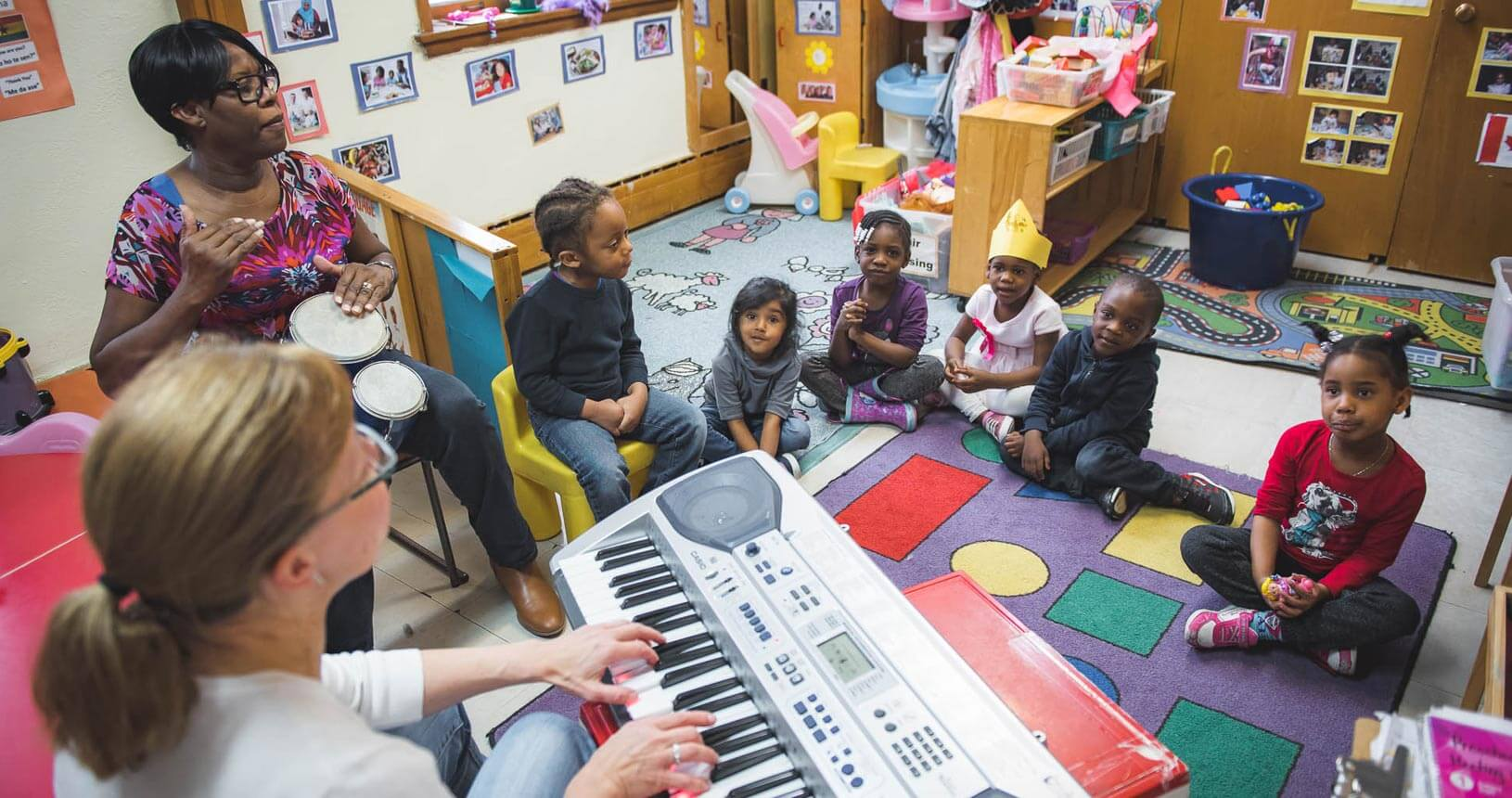 Two woman, one with a drum and the other with a keyboard, are teaching music class to six children sitting on the floor