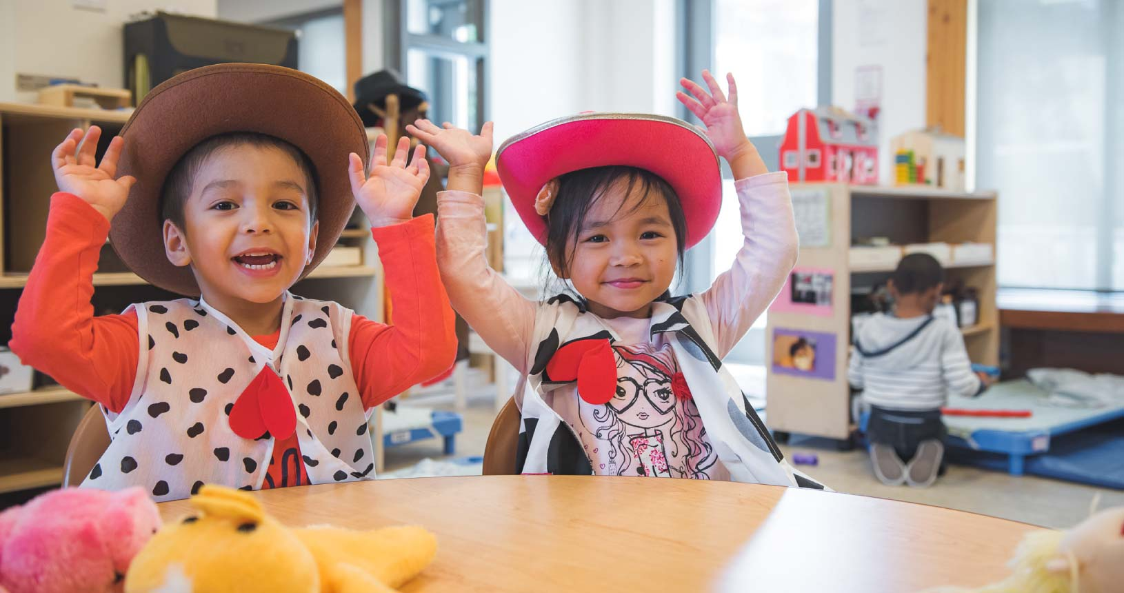 A young boy and girl, wearing cowboy hats, are having fun with their hands in the air