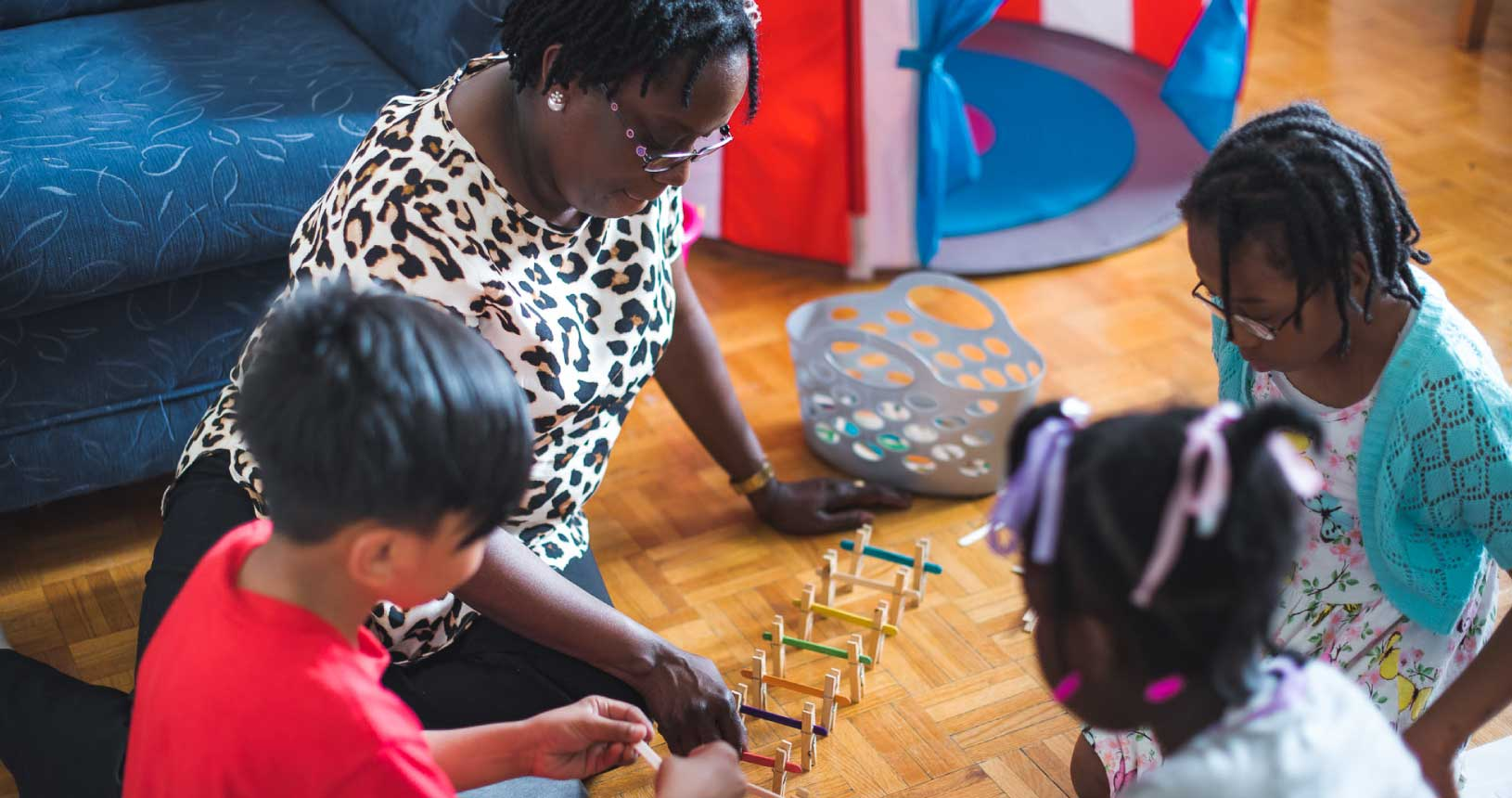 A woman and three children sit on the ground playing a game with popsicle sticks